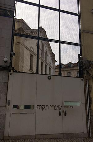 זהו שער הברזל בכניסה לחצר בית הכנסת. מבעד לסורגים ניתן לראות את מבנה בית הכנסת.